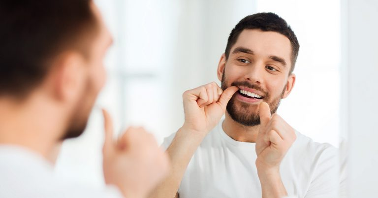 Man flossing his teeth in a mirror