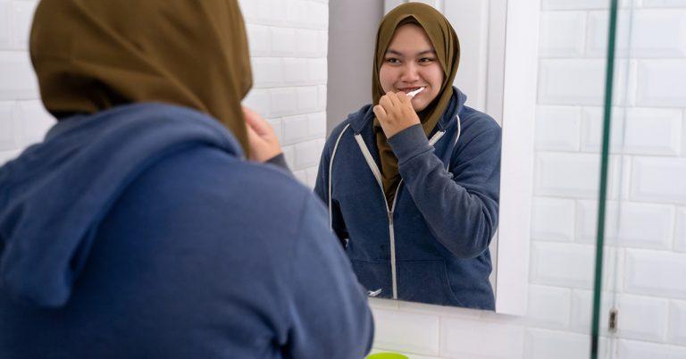 woman wearing hijab brush her teeth in bathroom sink